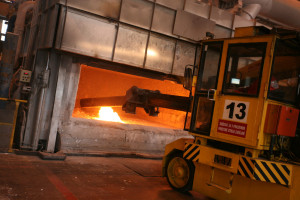Stirring metal in casting furnace.